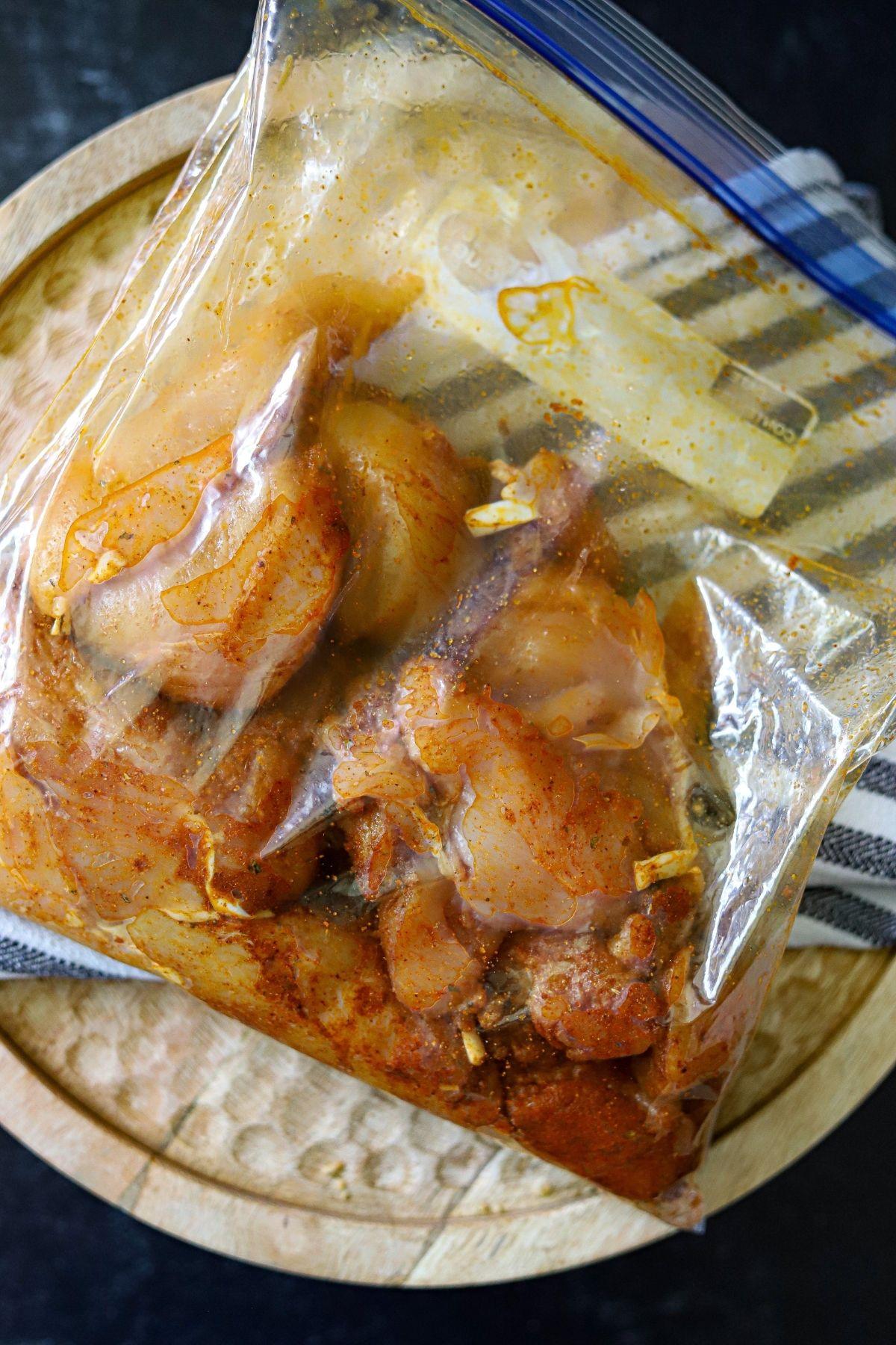 Raw chicken tenders coated in seasoning in a large ziplock bag