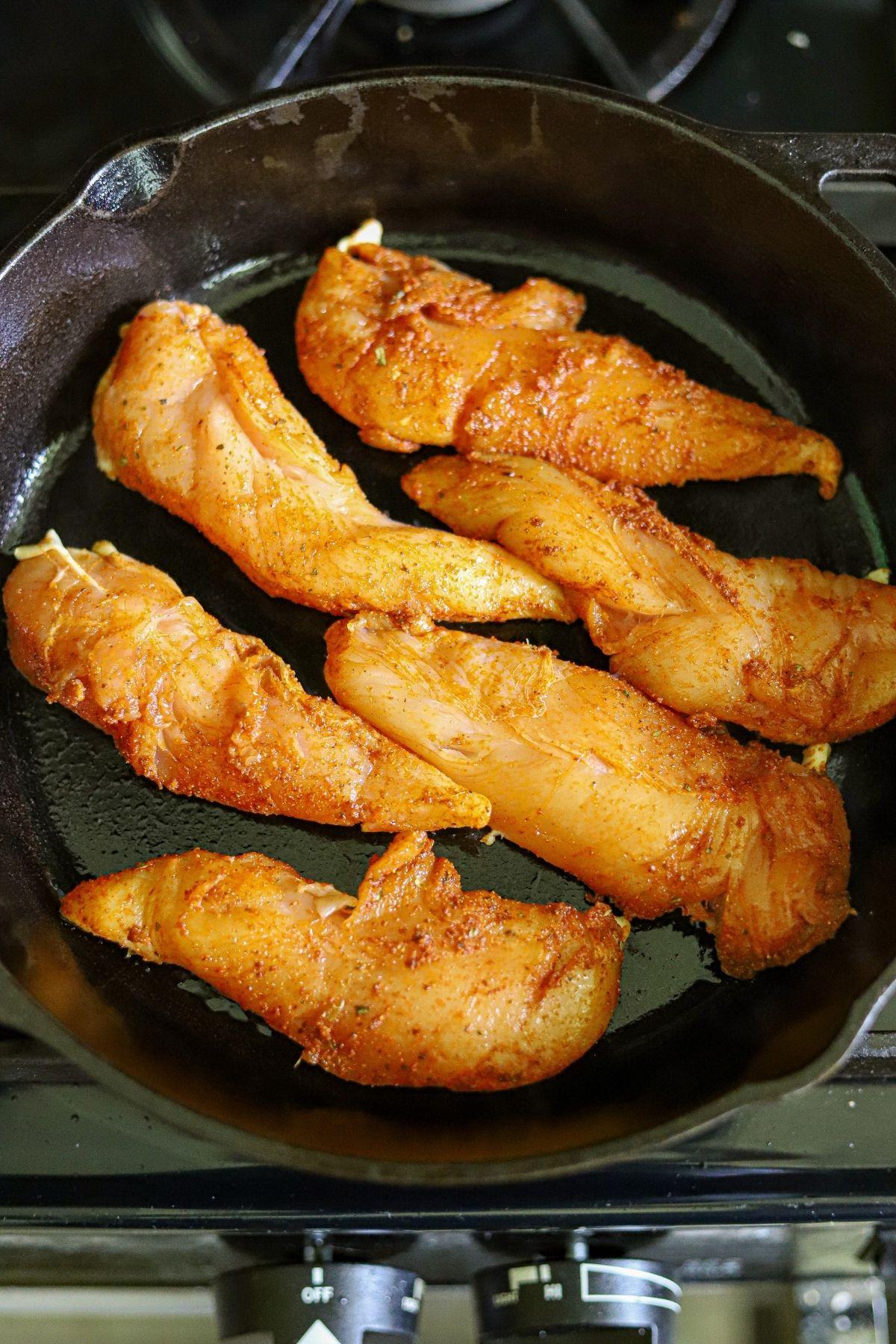 Chicken tenders coated in blackening seasoning, cooking in a cast iron skillet.