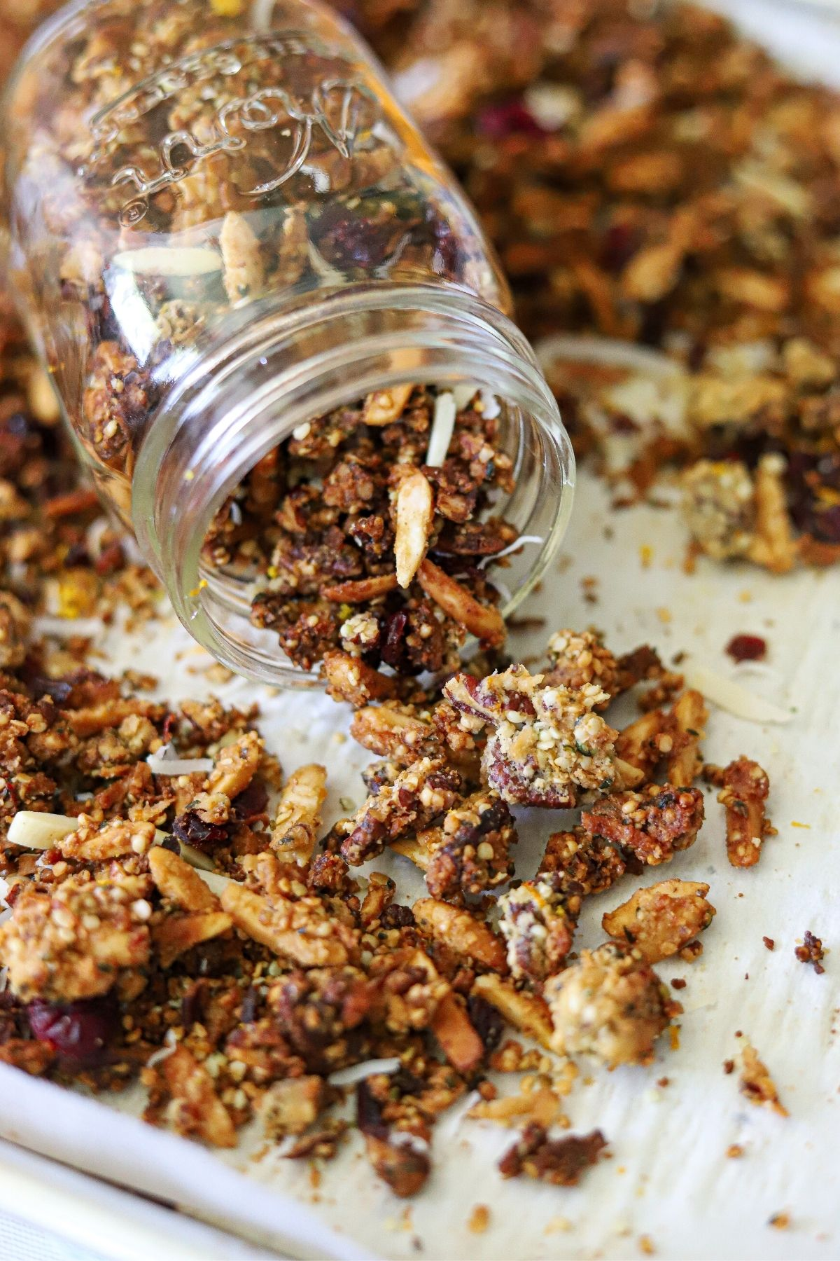 Homemade grain free granola sprinkled with orange zest and dried cranberries. The granola is spilling from a tipped glass jar