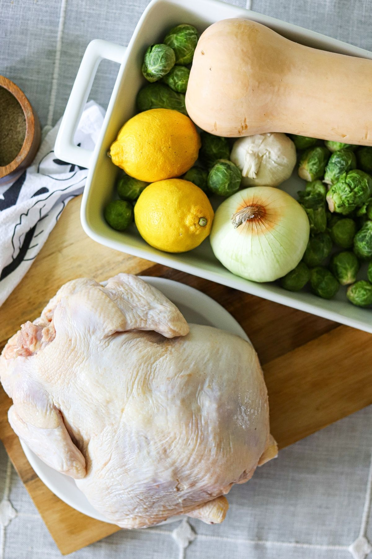 A whole chicken, raw, fresh brussels sprouts, a butternut squash, lemons, garlic, and onions on a wooden cutting board