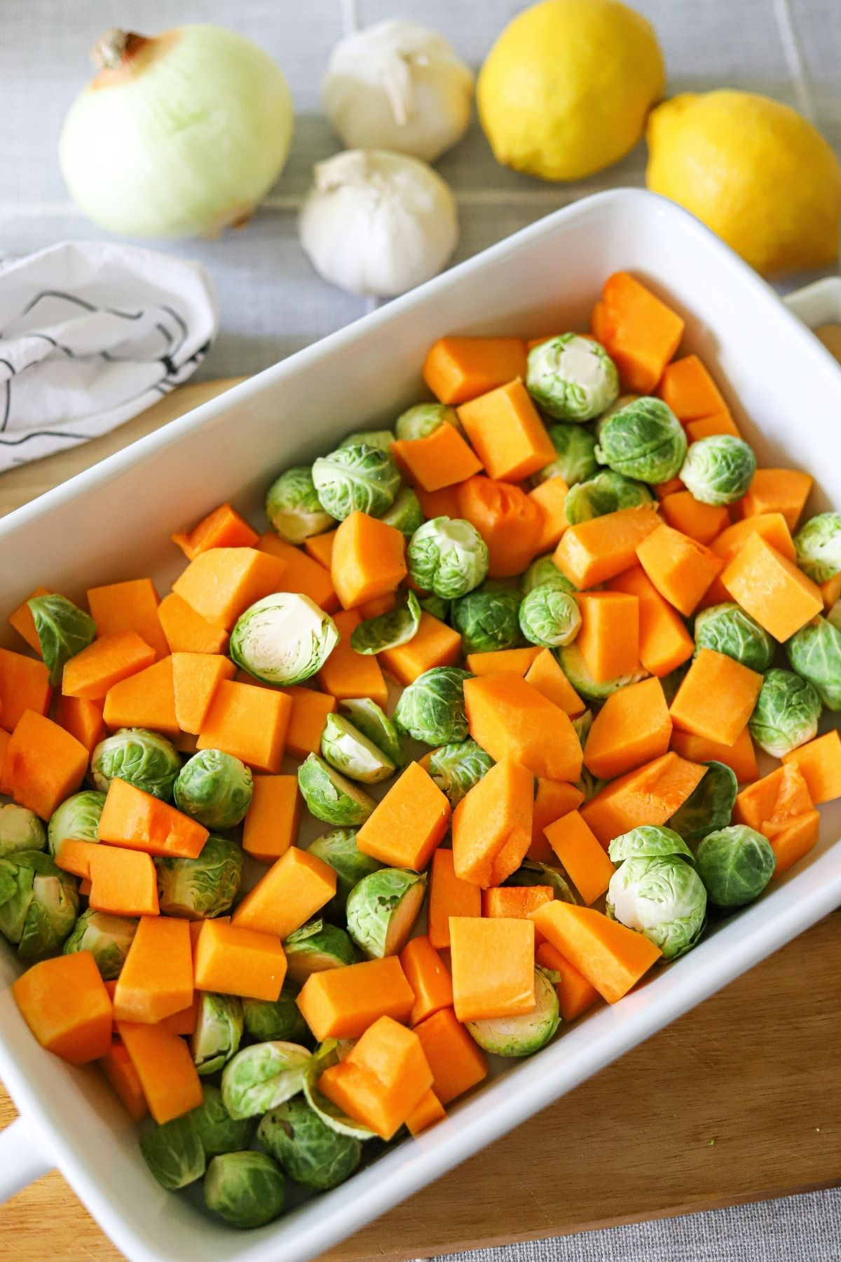 a baking dish full of cubed butternut squash, halved brussles sprouts, and peeled garlic cloves.