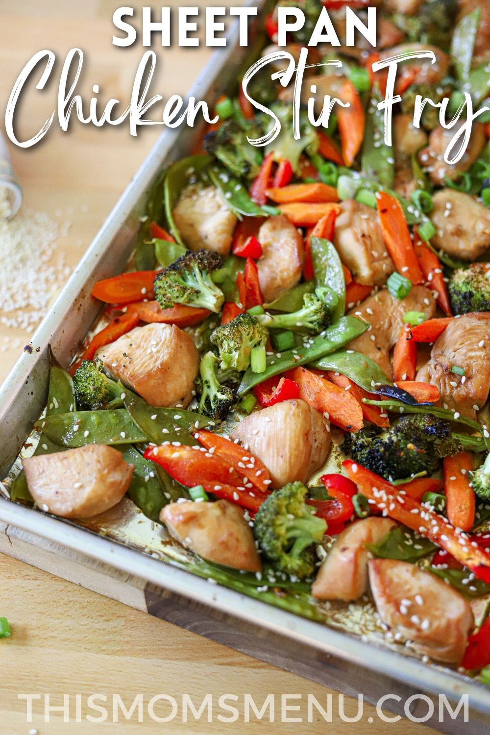 Chicken and vegetables cooked together on a sheet pan with a white text overlay.