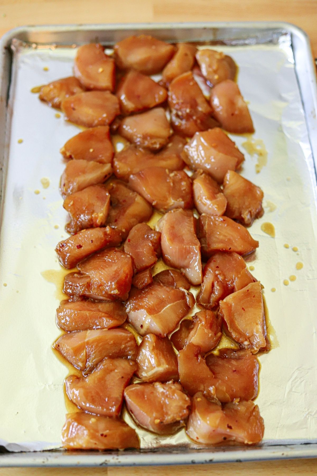 marinated chicken breast pieces in a single layer on a sheet pan.