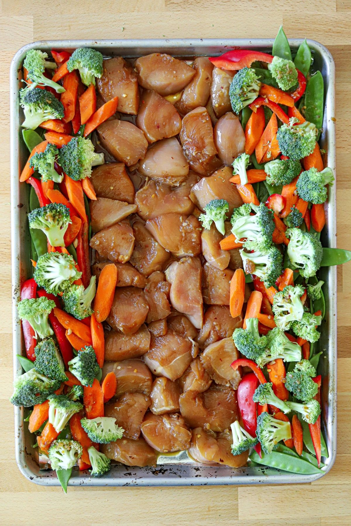 marinated chicken on a sheet pan surrounded by broccoli, carrots, red pepper, and snow peas.