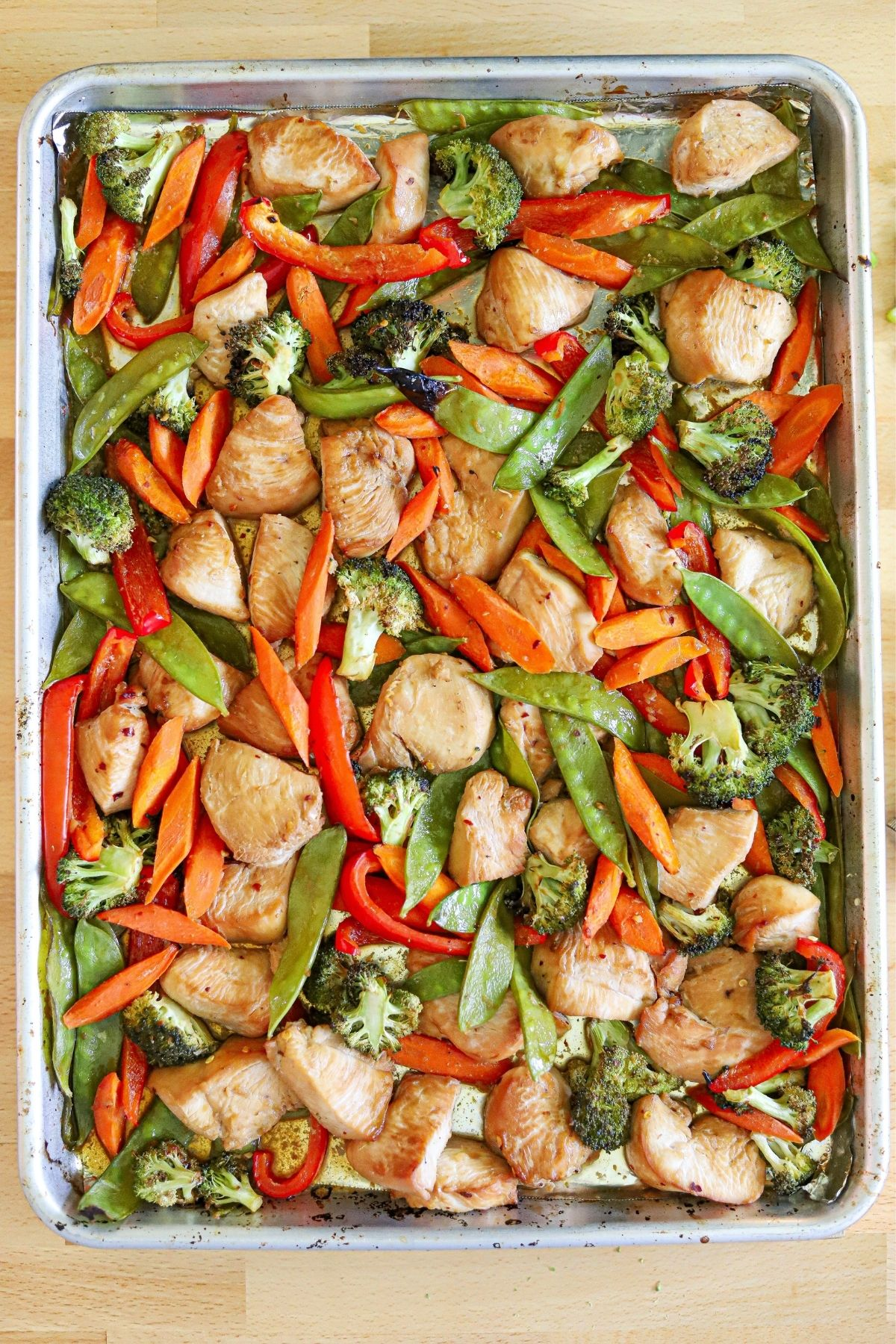 chicken and vegetables stirred together on a sheet pan