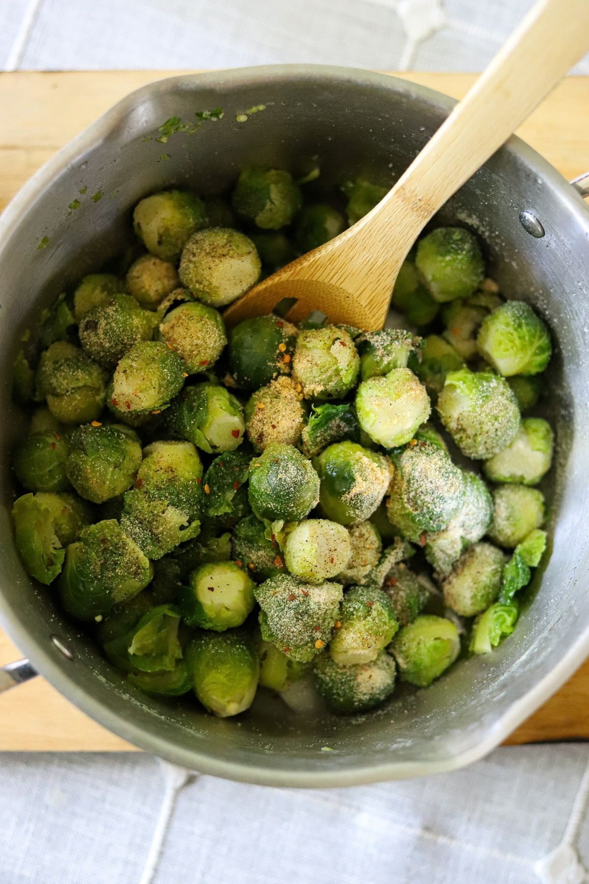 Brussels sprouts in a large pot, topped with various seasonings