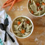 two bowls full of chicken soup with flat dumplings and carrots