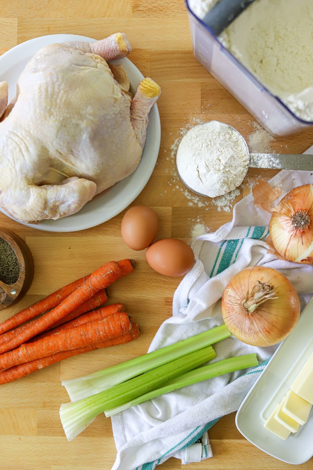 A butcher block filled with ingredients for chicken and dumplings including a whole chicken, flour, onions, carrots, celery, eggs, butter, and salt and pepper.