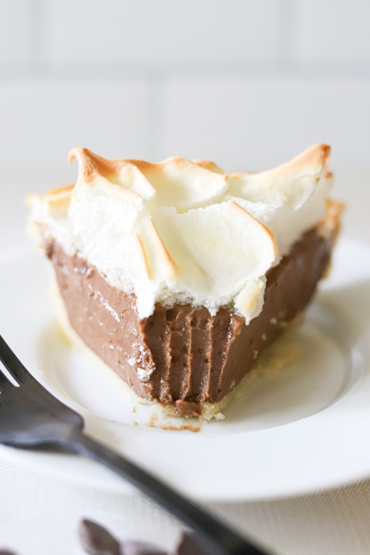 A slice of sugar free chocolate cream pie topped with meringue on a white plate. One bite has been taken.