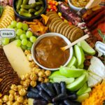 meats, cheeses, fruit, nuts, and crackers surrounding a bowl of caramel dip.