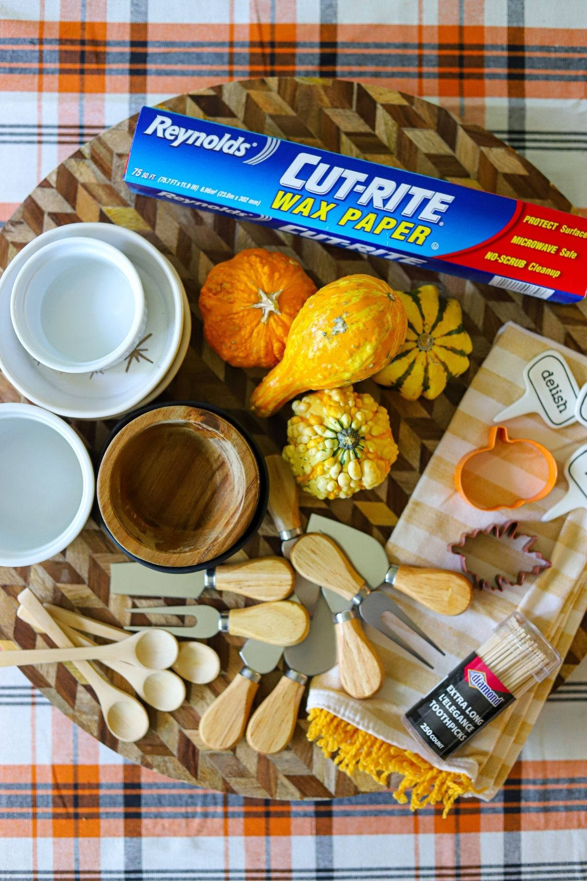 Equipment for a charcuterie board including small bowls, cheese kinves, cookie cutters, wax papers, spoons, and small pumpkins.