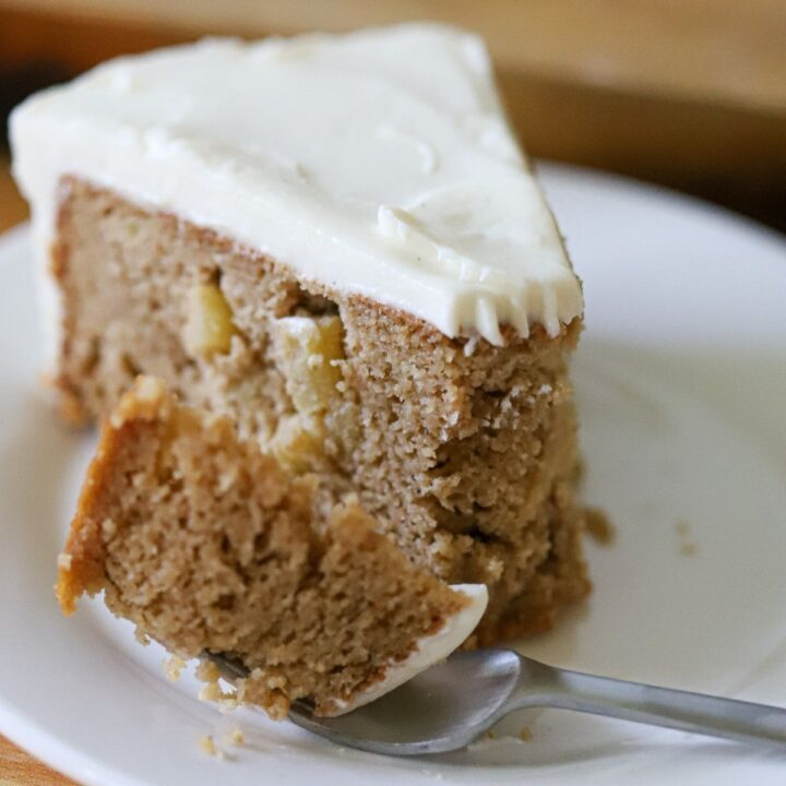 a slice of apple cake with cream cheese frosting on a white plate