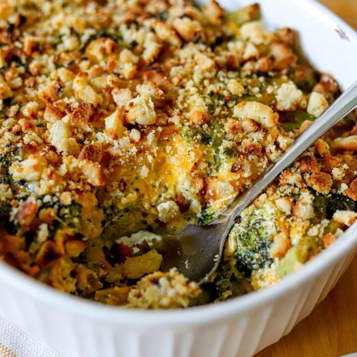 a white casserole dish full of cheesy broccoli