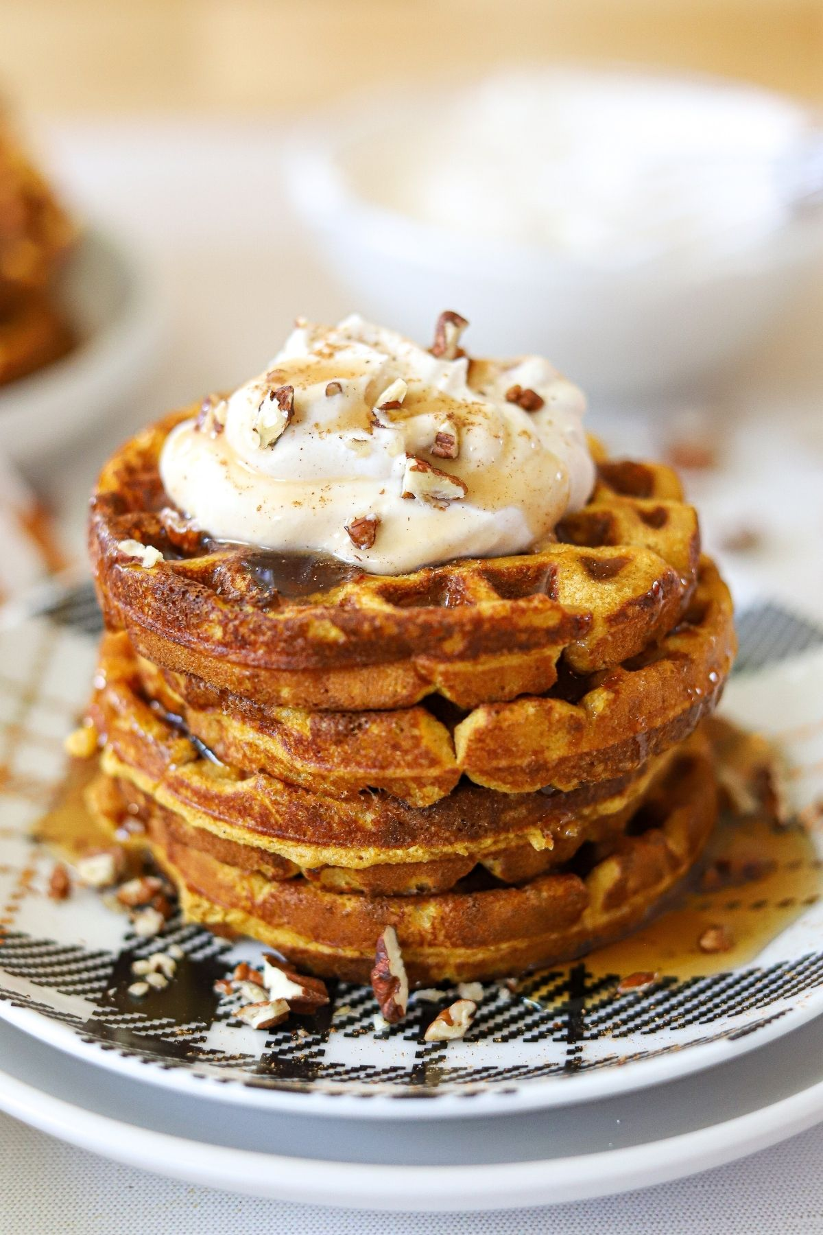 a stack of pumpkin waffles topped with chopped pecans, whipped cream, and sugar free maple syrup.