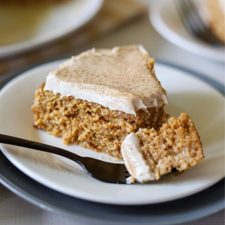 a slice of pumpkin tres leches on a plate with one bite taken